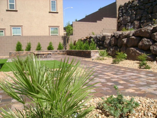 yard with rocks, small plants and stone paving